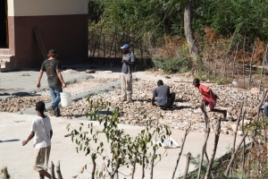 Andrew Hutchinson (on left) one of Dr. Ragone's students, carries a bucket of water to the Haitian workers on the playground work site.